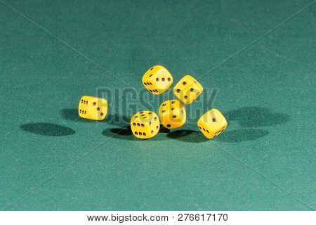 Six Yellow Dices Falling On A Isolated Green Table