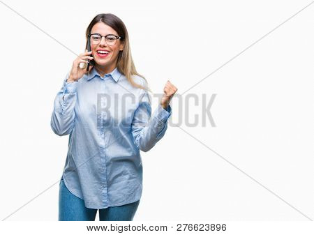 Young beautiful business woman speaking calling using smartphone over isolated background screaming proud and celebrating victory and success very excited, cheering emotion