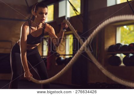 Fit, Sporty And Athletic Sportswoman Working In A Gym. Woman Training Using Battle Ropes. Sports, At