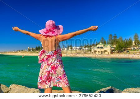 Carefree Woman In Hat With Open Arms At Cottesloe Beach, Perths Most Famous Town Beach, Western Aust