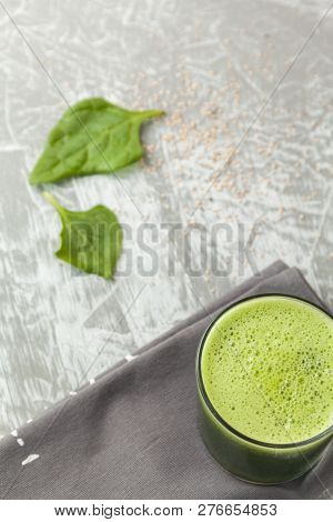 Fresh Green Spinach Smoothie In A Glass Cup On A Gray Wooden Surface. Flat Layout