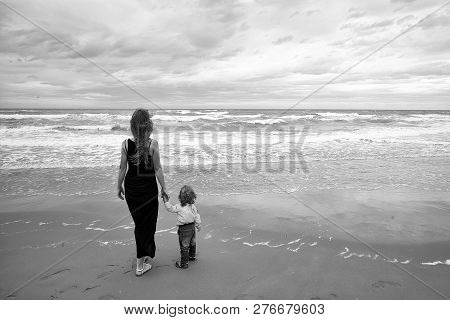 Mother In Black Dress And Son In Shirt Jeans Back View Standing On Sea Shore Beach Wet Sand Watching