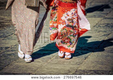 Two Japanese Women In Kimonos Walking In Kamakura, Japan With Their Shadows Following.