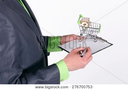 Blank Agreement Of Sale Or Buy House And Small Home In A Shopping Cart In A Real Estate Agent Hands