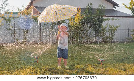 Watering Grass Background. Water Hoses Watering The Grass. Happy Boy Plays With Water Drops On Sunny