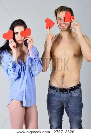 Couple in love happy with their relations. Sexual relations between people. Man sexy torso and woman in his shirt hold red hearts valentines cards. Love and relations concept. Romantic relations. poster
