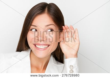 Listening ear: Business woman hearing secret gossip with hand to ear concept. Businesswoman listen to good news smiling. Beautiful happy mixed race Asian Caucasian young female professional in suit.