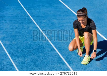 Sprinter runner getting ready to run on running lanes in track and field stadium outside. Woman athlete tying shoe laces for competition on blue tracks. poster