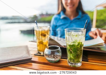 Two alcoholic cocktails at beach restaurant outside on dining table. Woman and closeup of drink mojito cocktail.