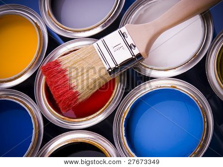 Cans with paint and brushes on the blue background