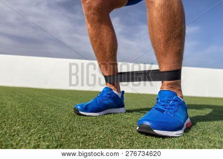 Resistance band workout man at fitness gym training calf muscles with rubber bands. Bodyweight exercises outdoor at park.