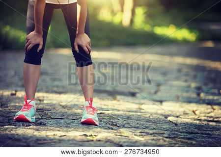 Tired Female Runner Taking A Rest After Running Hard In Countryside Road. Sweaty Athlete After Marat