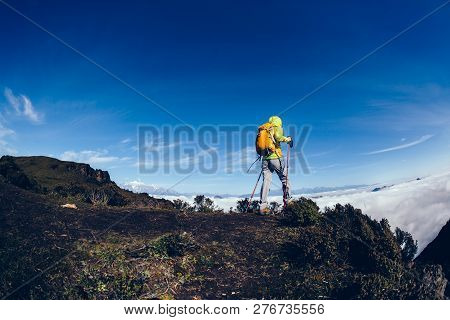 Young Woman Hiker On Mountain Peak Face The  Frozen Mountain Summits