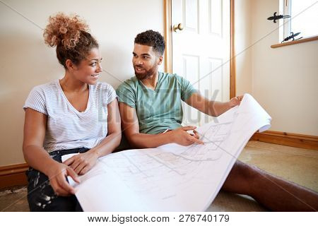 Couple Sitting On Floor Looking At Plans In Empty Room Of New Home