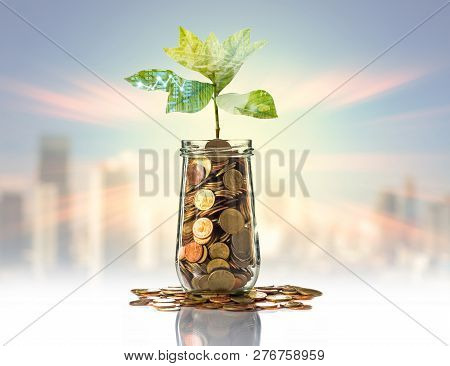 Double Exposure Of Gold Coins And Seed In Clear Bottle With Trading Graph On Photo Blurred Cityscape