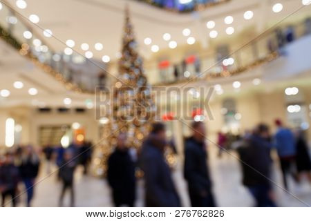 Christmas Shopping Circus: Blurred Scene With Dandering Pedestrians Around Christmas Decoration Tree