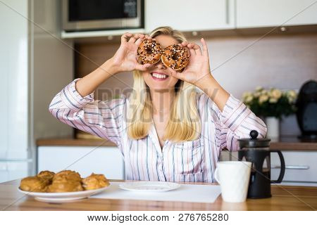Portrait Of Funny Young Woman Covering Her Eyes With Donuts In Modern Kitchen