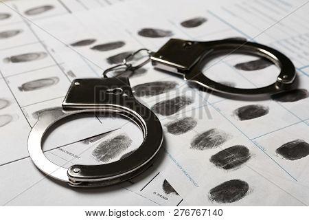 Police Handcuffs And Criminal Fingerprints Card, Closeup