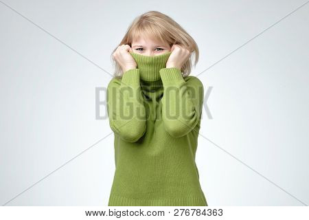 Young Blonde Woman Wearing A High Neck Green Sweater Hiding Her Face
