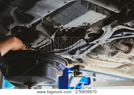 Vehicle Lift Up By Hydraulic For Motor Oil Change & Transmission Inspection. Changing  Engine Oil In