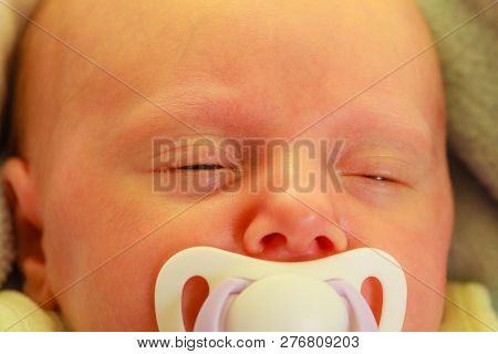 Infant Care, Beauty Of Childhood Concept. Little Newborn Baby Sleeping Calmly In Bed With Teat In Mo