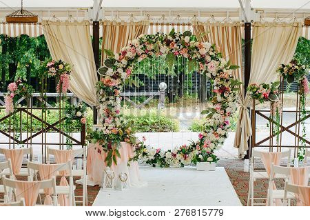 Beautiful Wedding Set Up. Area Of The Wedding Ceremony. Round Arch, White Chairs Decorated With Flow