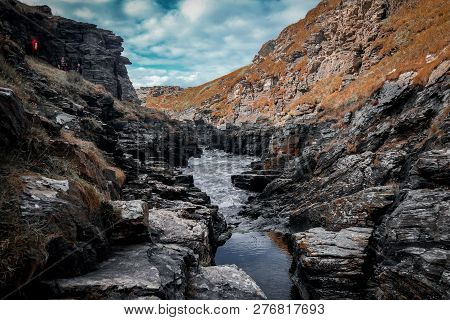 Colourful Cliffs Surround The Rocky Valley In Cornwall, Tintagel. The Water Splashes Through The Roc