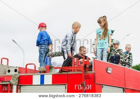 Horki, Belarus - July 25, 2018: Children Of Different Ages Play On The Red Cars Of The Rescue Servic