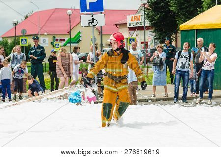 Horki, Belarus - July 25, 2018: Lifesaver Of Service Rescue 112 Pulls Fire Hose On A Holiday In The