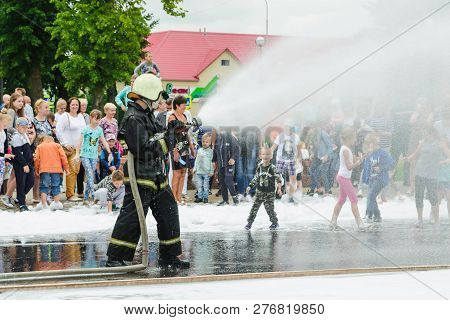 Horki, Belarus - July 25, 2018: Lifesaver Of Service Rescue 112 Pours Water From A Fire Hose During