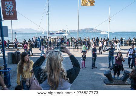 July 7 2017 - San Francisco, California: Tourist Woman Takes Photos Of Alcatraz From Pier 39 At A Bu