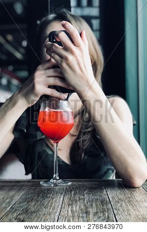 Young Caucasian Woman Holds Smart Phone In Front Of The Face Sitting On The Table In Cafe, Bocal Wit