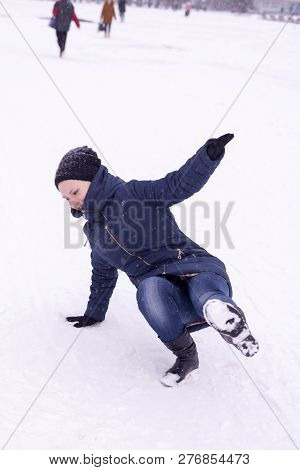 The Girl Slipped On Ice Covered With Snow, Falling And Injury In The Winter