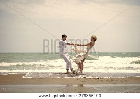 Beautiful Happy Young Wedding Pair Of Boy And Girl In White Spinning On Ocean Beach Coast On Windy W