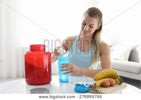 Young Woman Preparing Protein Shake At Table In Room