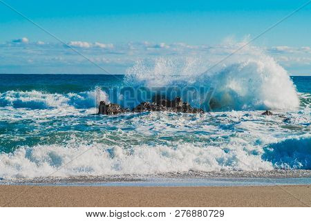 Seascape of waves violently crash against rocks as they roll into shore under a beautiful blue sky. poster