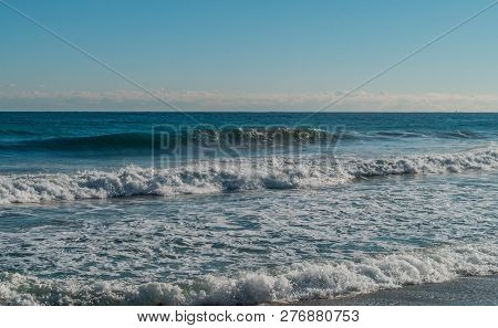 Seascape Of Whitecaps And Waves As Tide Rolls In To Shore On Beautiful Winter Morning Under Partly C