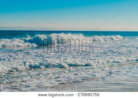 Seascape Of Whitecaps And Waves As Tide Rolls In To Shore On Beautiful Winter Morning Under Partly B
