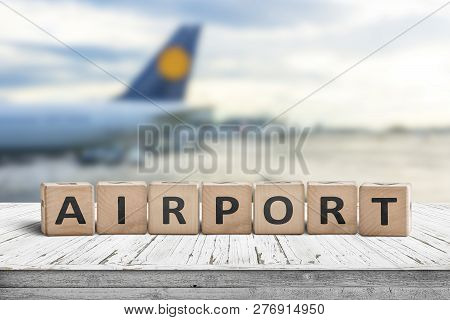 Airport Word Sign On A Wooden Surface With A Plane In The Background