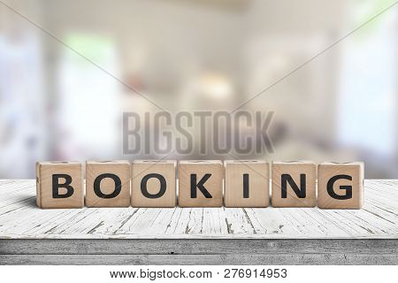 Booking Sign On A Wooden Desk In A Room With A Bright Blurry Background