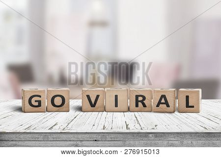 Go Viral Message Sign On A Wooden Table In A Bright Room