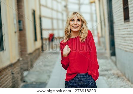 Happy Young Blond Woman Walking Down The Street. Smiling Blonde Girl With Red Shirt Standing Outdoor