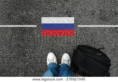 A Man With A Shoes And Backpack Is Standing On Asphalt Next To Flag Of Russia And Border