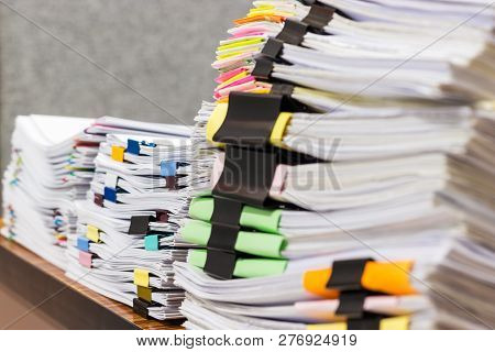 Pile Of Unfinished Document On Office Desk. Stack Of Homework Assignment Archive With Colorful Paper