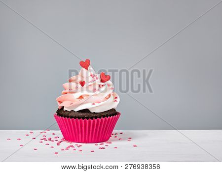 Valentines Day Cupcake Treat With Buttercream Icing And Heart Sprinkles On A Grey Background