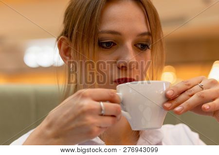 Girl Office Manager In A Business Blouse Thoughtfully Drinks A Cappuccino During A Coffee Break In T