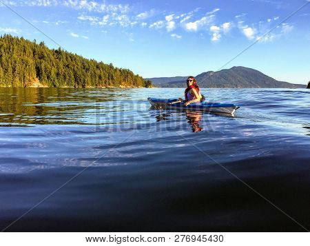 A Girl Enjoying Kayaking On The Beautiful And Calm Ocean Waters Of Howe Sound, Off Of Gambier Island