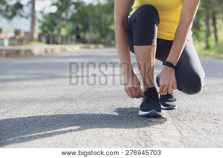 A Young Woman Stopped To Tie A String While Running In The Stadium, Fitness Woman Runner Tying Shoel