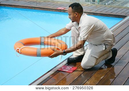 Hands of the rescuer with lifebuoy in pool. Hotel worker throws a lifeline to a drowning pool. Salvation of a sinking person. Life ring in swimming pool. Red lifebuoy pool ring. poster