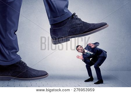 Young handsome businessman getting crushed by a big formal shoe